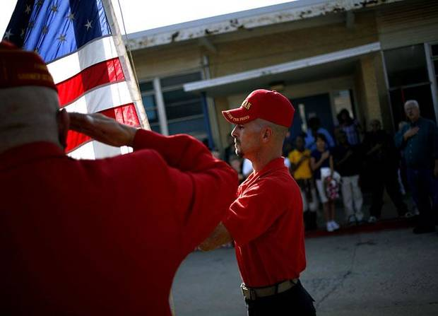 Michael Breeden, a Marine Corps League Member, takes down the flag at Johnson Elementary School during a presentation  by the group in Oklahoma City on Wednesday, Nov. 11, 2009. The older flag was replaced with a new one during the presentation. By John Clanton, The Oklahoman ORG XMIT: KOD