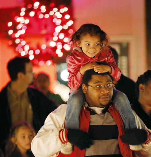Lae-lee Amevor sits on the shoulders of her father, Solomon Amevor, while waiting for a sleigh ride during the holiday lighting ceremony at Rose State College. Photos by Nate Billings, The Oklahoman
