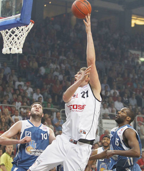 Brose Basket's Tibor Pleiss, center, shoots between the defense from Deutsche Bank Skyliners during Bundesliga action in 2010. AP photo