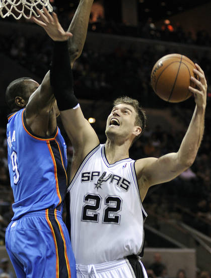 San Antonio Spurs' Tiago Splitter (22), of Brazil, shoots over Oklahoma City Thunder's Serge Ibaka, of Congo, during the first half of an NBA basketball game, Monday, March 11, 2013, in San Antonio. (AP Photo/Darren Abate) ORG XMIT: TXDA105