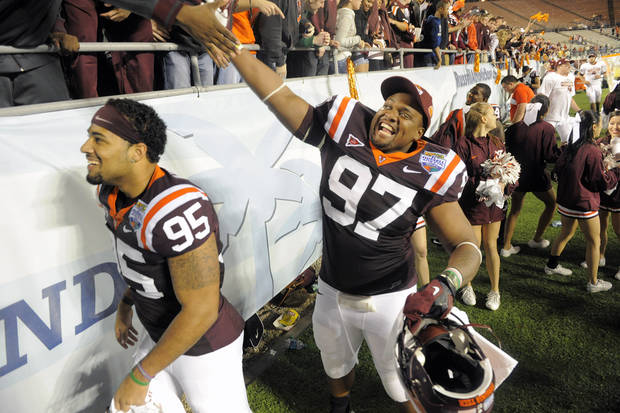 Virginia Tech defensives tackle Zack McCray, left, and Kris Harley, right, celebrate with fans following their 13-10 win in overtime of an NCAA college football Russell Athletic Bowl game against Rutgers, Friday, Dec. 28, 2012, in Orlando, Fla. (AP Photo/Brian Blanco)