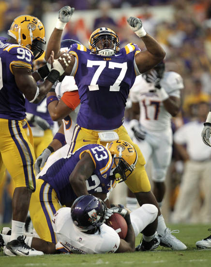 LSU defensive tackle Josh Downs (77) celebrates after he and Stefoin Francois tackled Northwestern State running back Sidney Riley for a loss during the first quarter of their NCAA college football game in Baton Rouge, La., Saturday, Sept. 10, 2011. (AP Photo/Gerald Herbert)