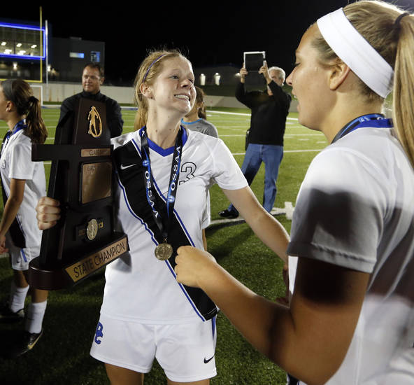 Deer Creek player Rachel Landes reaches for teammate Sophia Brazil as she holds the championship trophy after the Class 5A girls state soccer championship game between Deer Creek and Carl Albert on Friday, May 10, 2013 in Noble, Okla.  Photo by Steve Sisney, The Oklahoman