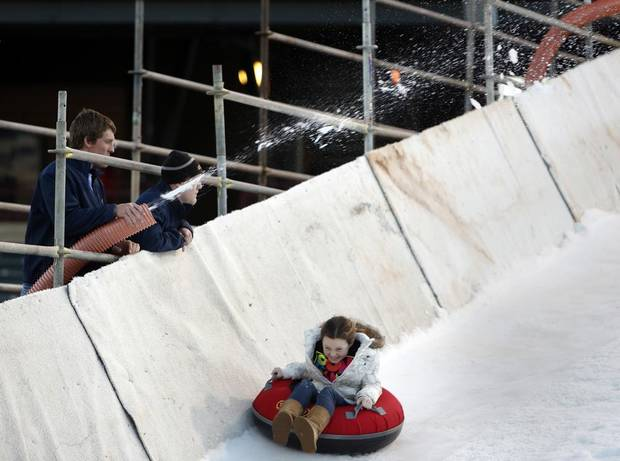 Employees spray snow on a slope as Macy McColl, 9, rides down at Chickasaw Bricktown Ballpark in Oklahoma City, Saturday, Nov. 24, 2012.  Photo by Garett Fisbeck, The Oklahoman