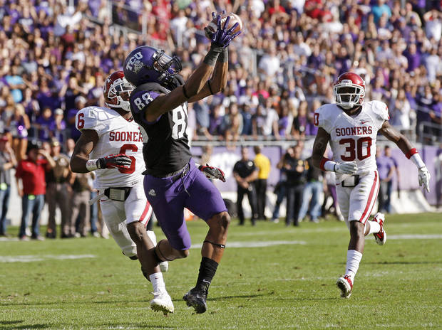TCU's Cam White (88) catches a pass in front of Oklahoma's Demontre Hurst (6) and Javon Harris (30) late in a college football game between the University of Oklahoma Sooners (OU) and the Texas Christian University Horned Frogs (TCU) at Amon G. Carter Stadium in Fort Worth, Texas, Saturday, Dec. 1, 2012. Oklahoma won 24-17. Photo by Bryan Terry, The Oklahoman