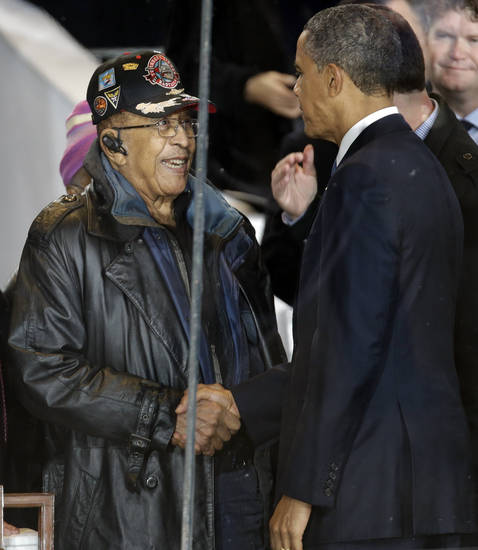President Barack Obama speaks to a former member of the Tuskegee airman in the presidential box during the inaugural parade, Monday, Jan. 21, 2013, in Washington. Thousands  marched during the 57th Presidential Inauguration parade after the ceremonial swearing-in of President Barack Obama. (AP Photo/Gerald Herbert) ORG XMIT: DCMS167