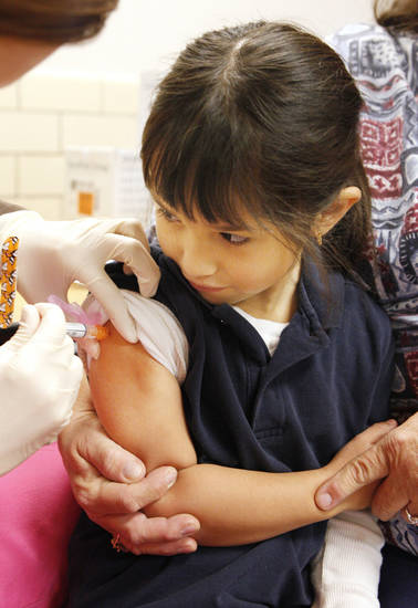 Kindergarten student Rosa Melendez, 6, gets flu shot Wednesday at Mark Twain Elementary. Photo by Paul B. Southerland, The Oklahoman <strong>PAUL B. SOUTHERLAND</strong>