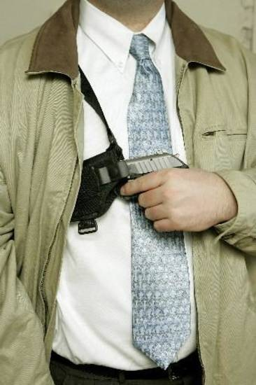 Photo illustration of someone concealing a gun by Steve Gooch.