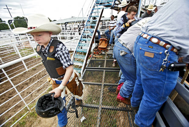 Bowde 'Shorty Smalls' Sawyer walks the back of the bucking chutes before his bull ride during the Youth Rodeo Bible Camp at the Three Crosses Arena on Wednesday in Union Valley.