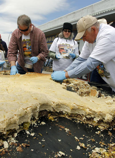 Volunteers cut small burgers out of a giant hamburger during the Burger Day Festival in El Reno Saturday. <strong>PAUL HELLSTERN - Oklahoman</strong>
