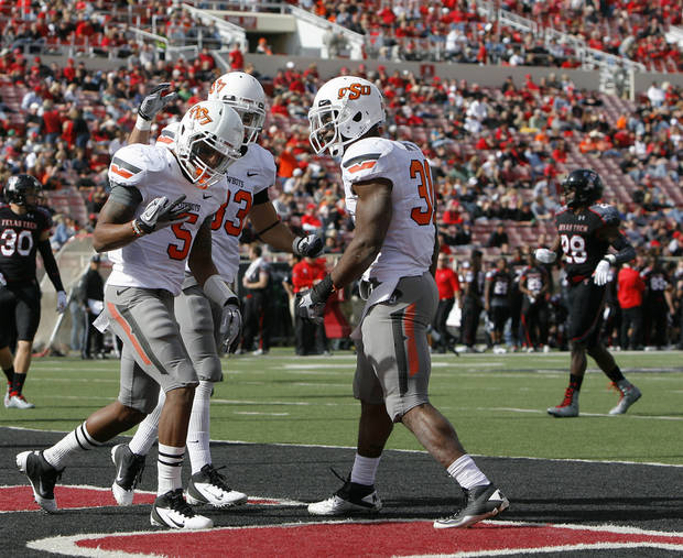 Oklahoma State's Josh Stewart (5) celebrates a touchdown with Colton Chelf (83) and Jeremy Smith (31) during a college football game between Texas Tech University (TTU) and Oklahoma State University (OSU) at Jones AT&T Stadium in Lubbock, Texas, Saturday, Nov. 12, 2011.  Photo by Sarah Phipps, The Oklahoman  ORG XMIT: KOD