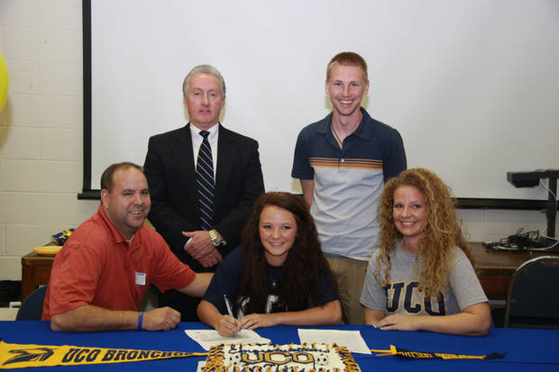 Choctaw soccer player Caitlin Bond, seated center, signs her letter of intent with the University of Central Oklahoma with her mother, Cynthia White, and father, Ron White at her side. Standing on the back row from left are coach Donnie Hughes, Bond's competitive league coach, and Choctaw High School coach Chris Maggart.