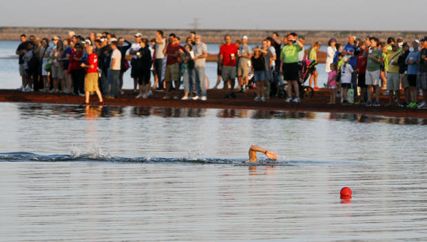 Spectators watch as the first athlete finishes his swim event during the Redman Triathlon in Oklahoma City, OK, Saturday, September 22, 2012,  By Paul Hellstern, The Oklahoman
