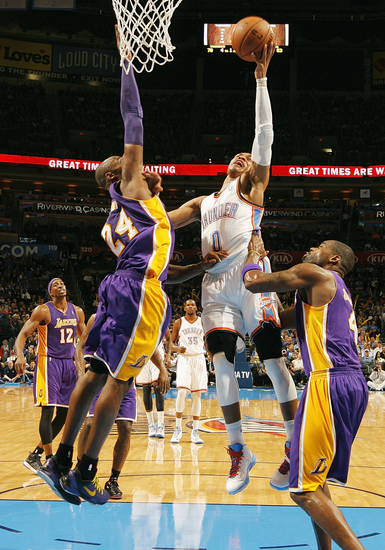 Oklahoma City's Russell Westbrook (0) takes the ball to the hoop against Los Angeles' Kobe Bryant (24) and Antawn Jamison (4) during an NBA basketball game between the Oklahoma City Thunder and the Los Angeles Lakers at Chesapeake Energy Arena in Oklahoma City, Friday, Dec. 7, 2012. Oklahoma City won, 114-108. Photo by Nate Billings, The Oklahoman