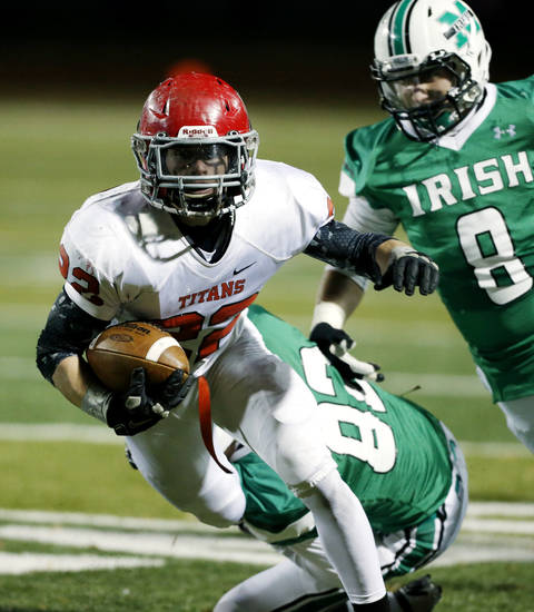 Titan running back Garrett Asher (22) eludes the tackle of Austin Hopfer (82) and Bobby Sweeney (8) as the Bishop McGuinness Irish play the Carl Albert Titans in a Class 5A semi-final playoff game at Harve Collins Field on Friday, Nov. 23, 2012  in Norman, Okla. Photo by Steve Sisney, The Oklahoman