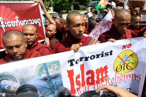 Buddhist monks hold banners as they stage a rally outside the Embassy of Bangladesh Friday, Oct. 5, 2012, in Yangon, Myanmar. More than 100 Buddhist monks demonstrated in front of the Bangladesh embassy in capital Yangon on Friday, condemning the recent attacks against Buddhist temples and houses in Bangladesh. (AP Photo/Khin Maung Win)