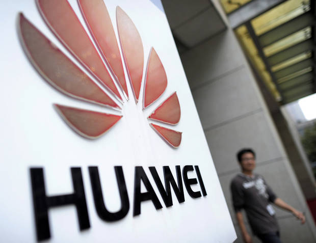 In this Monday, Oct. 8, 2012 photo, a man walks near a logo at a R&D center of Huawei Technologies Inc. in Wuhan, in central China's Hubei province. Eager to expand in the United States, China�s biggest technology companies face American anxiety about security and rising Chinese competition. (AP Photo) CHINA OUT