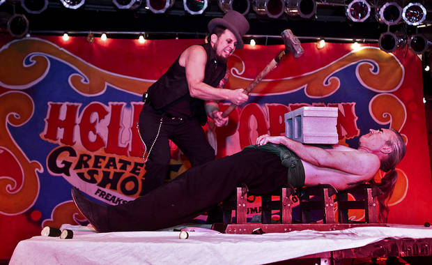 Bryce 'The Govna' Graves swings a sledgehammer to break a block on Zamora the torture king who lays on a bed of razor sharp swords during the Hellzapoppin show at the Diamond Ballroom on Friday, Dec. 11, 2009, in Oklahoma City, Okla.   Photo by Chris Landsberger, The Oklahoman