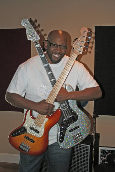 Musician/former University of Oklahoma (OU) college basketball/NBA basketball player Wayman Tisdale with bass guitars