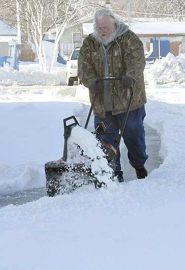 Ike Nordsieck clears the sidewalks at the city hall in Enid, Oklahoma Tuesday, Feb. 26, 2013. The city received an estimated 10 inches of snow and wind damage leaving 90 per cent of the town without power. (AP Photo/Enid News &amp; Eagle, Billy Hefton)  ORG XMIT: OKENI103
