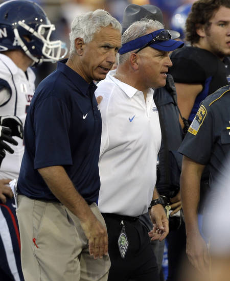 Connecticut head coach Paul Pasqualoni, left, and Buffalo head coach Jeff Quinn walk off the field after an NCAA college football game on Saturday, Sept. 28, 2013, in Buffalo, N.Y. Buffalo won, 41-12. (AP Photo/Mike Groll)