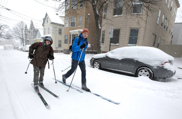 Andre Tranchemantague, left, and Will Guerette, ski on a snow-covered road as they make there way to a bar during the early stages of a snow storm, Friday, Feb. 8, 2013, in Portland, Maine.  A snowstorm sweeping into Maine already has dumped half-a-foot of snow around Portland and contributed to a 19-car pileup. And it's just getting started. Chris Legrow from the National Weather Service says a blizzard warning is issued Friday evening for the southern coast, when the main storm arrives. The forecast calls for up to 2 feet of snow and winds gusting to 50 mph. (AP Photo/Robert F. Bukaty) ORG XMIT: MERB101