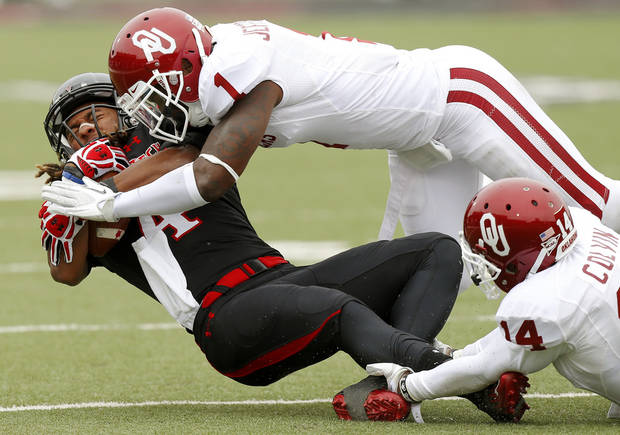 Texas Tech's Bradley Marquez (4) is brought down by Oklahoma's Tony Jefferson (1) and Aaron Colvin (14) during a college football game between the University of Oklahoma (OU) and Texas Tech University at Jones AT&T Stadium in Lubbock, Texas, Saturday, Oct. 6, 2012. Photo by Bryan Terry, The Oklahoman