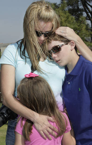 Jennifer Burton and her children Walker, 12, and Graecin, 6, hug at the chair of her father, David Walker, after the Day of Remembrance Ceremony, Tuesday, April 19, 2011.  This was the 16th annual Oklahoma City Bombing Memorial ceremony.   Photo by David McDaniel, The Oklahoman
