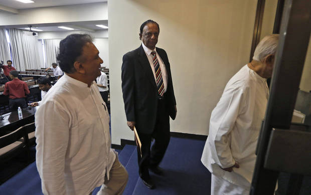 Sri Lankan opposition lawmakers John Amaratunga, center, and Lakshman Kirriella, left, leave after addressing the media at Parliament in Colombo, Sri Lanka, Friday, Dec. 7, 2012. Sri Lankan opposition lawmakers Friday withdrew from a committee looking into impeachment charges against Chief Justice Shirani Bandaranayake, saying the process is flawed and unfair. (AP Photo/Eranga Jayawardena)