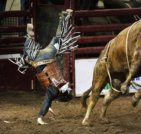 Rowdy Rice is flipped through the air as he lands after being thrown from this bull during the Saturday afternoon session, 2nd go-round of the 42nd International Finals Rodeo (IFR) in the arena at State Fair Park, Jan. 14, 2012,    Photo by Jim Beckel, The Oklahoman