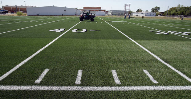 Workers install artificial turf on the practice field at Moore High School on Thursday.  Photo by Steve Sisney, The Oklahoman