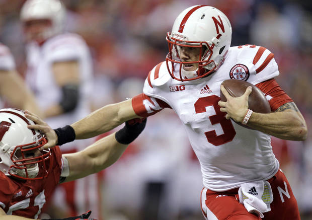 Nebraska quarterback Taylor Martinez pushes off Wisconsin defensive lineman Tyler Dippel during the first half of the Big Ten championship NCAA college football game Saturday, Dec. 1, 2012, in Indianapolis. (AP Photo/Michael Conroy) ORG XMIT: NAS136