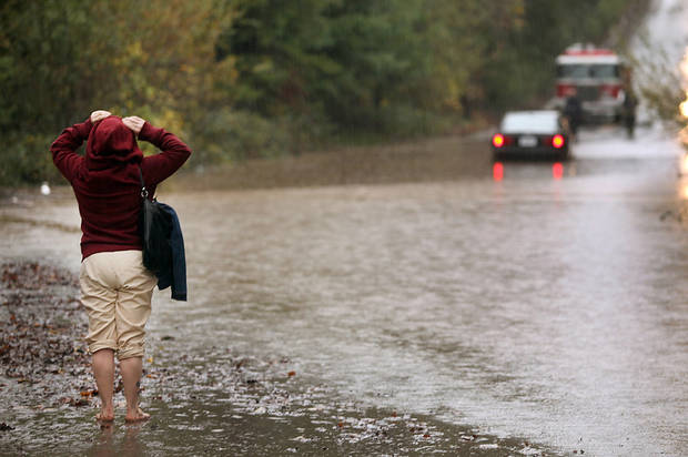 Kimberly Masklyne looks at her flooded car, Sunday Dec. 2, 2012, in Windsor, Calif. The National Weather Service issued flood warnings yesterday for both the Napa and Russian rivers. (AP Photo/The Press Democrat, Kent Porter)