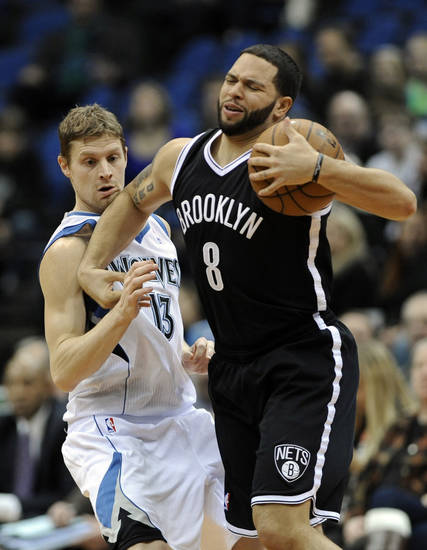 Minnesota Timberwolves' Luke Ridnour, left, gets an elbow to the chin as he defends against Brooklyn Nets' Deron Williams in the first half of an NBA basketball game on Wednesday, Jan. 23, 2013, in Minneapolis. (AP Photo/Jim Mone)