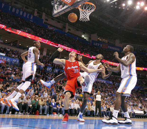 Los Angeles Clippers power forward Blake Griffin (32) battles under the basket with Oklahoma City Thunder small forward Kevin Durant (35), Oklahoma City Thunder power forward Serge Ibaka (9) and Oklahoma City Thunder center Kendrick Perkins (5) during the NBA basketball game between the Oklahoma City Thunder and the Los Angeles Clippers at Chesapeake Energy Arena on Wednesday, March 21, 2012 in Oklahoma City, Okla.  Photo by Chris Landsberger, The Oklahoman