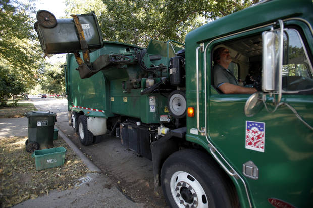Norman city sanitation workers pick up trash, while a bin for recyclables is set out for pickup by Waste Management. City officials are debating whether sanitation workers should take over operation of the curbside recycling service. OKLAHOMAN ARCHIVES