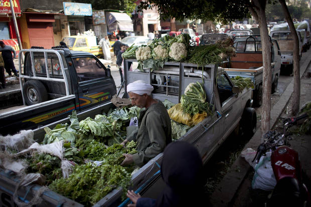 An Egyptian street vendor sits at the back of a pickup truck along with vegetables displayed for sale, in Cairo, Egypt, Thursday, Jan. 3, 2013. (AP Photo/Nasser Nasser)