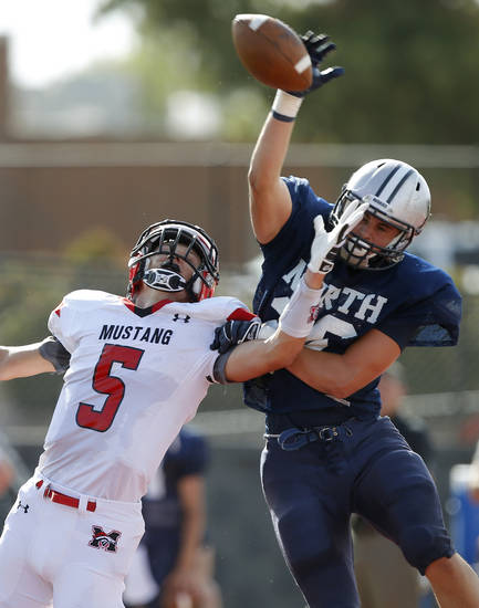 Edmond North's David Wright, at left, breaks up a pass intended for Mustang's Colton Hadlock during a high school football scrimmage at Mustang, Thursday, August 29, 2013. Photo by Bryan Terry, The Oklahoman