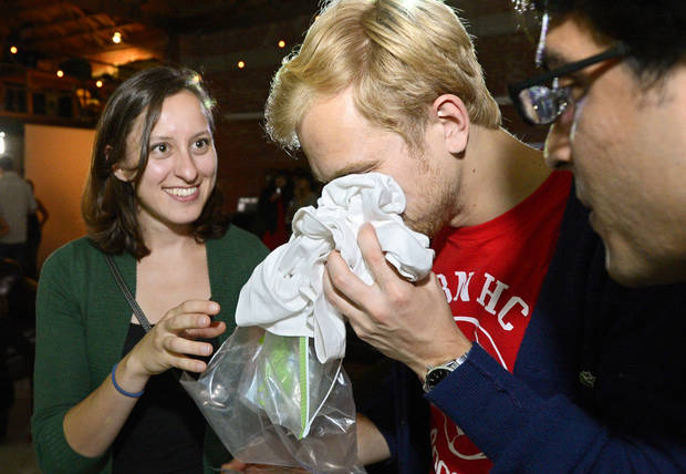 Konstantin Bakhurin, center, smells a shirt as Martina Desalvo, left, and Neelroop Parikfhak look on during a pheromone party, Friday, June 15, 2012, in Los Angeles. The get-togethers, which have been held in New York and Los Angeles and are planned for other cities, require guests to submit a slept-in T-shirt that will be sniffed by other participants. Then you can pick your partner based on scent. (AP Photo/Mark J. Terrill)