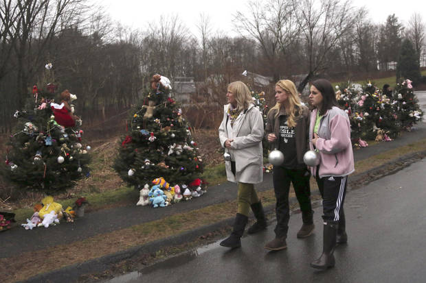 Mourners carry ornaments to decorate the Christmas trees at one of the makeshift memorials for the Sandy Hook Elementary School shooting victims, Monday,Dec. 17, 2012 in Newtown, Conn. Authorities say gunman Adam Lanza killed his mother at their home on Friday and then opened fire inside the Sandy Hook Elementary School in Newtown, killing 26 people, including 20 children, before taking his own life. (AP Photo/Mary Altaffer) ORG XMIT: CTMA106