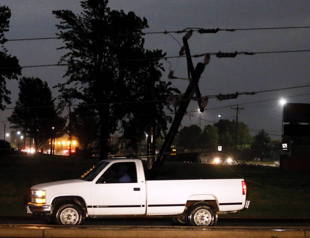 A truck drives past a silhouetted downed power pole at SW 44th and Council in Oklahoma City, Friday, May 31, 2013. Severe Thunderstorms brought tornadoes, high winds, heavy rain and hail to central Oklahoma on Friday. Photo by Nate Billings, The Oklahoman