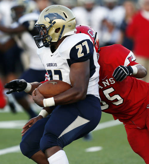 Southmoore's Alex James (27) carries the ball as Carl Albert's Kyler Walker (55) moves in for the tackle during a high school football game between Carl Albert and Southmoore in Midwest City, Okla., Friday, Aug. 31, 2012. Photo by Nate Billings, The Oklahoman