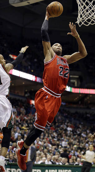 Chicago Bulls' Taj Gibson (22) dunks the ball past Milwaukee Bucks' Monta Ellis, left, during the first half of an NBA basketball game Wednesday, Jan. 30, 2013, in Milwaukee. (AP Photo/Jeffrey Phelps)