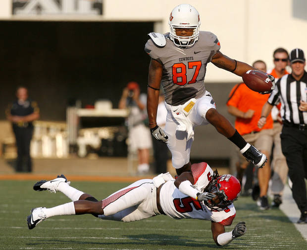 Oklahoma State's Tracy Moore leaps over Louisiana-Lafayette's Dwight Bentley (5) during Saturday's game in Stillwater. Photo by Sarah Phipps, The Oklahoman