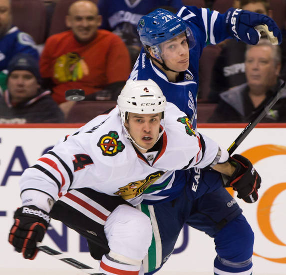 Chicago Blackhawks' Niklas Hjalmarsson, left, of Sweden, and Vancouver Canucks' Mason Raymond battle to get to the puck during the first period of an NHL hockey game in Vancouver, British Columbia, on Friday, Feb. 1, 2013. (AP Photo/The Canadian Press, Darryl Dyck)