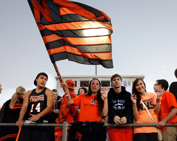 Norman High School Fan Taylor Hudson holds a Tiger flag as her team takes the field in high school football as the Norman High School Tigers play the Edmond Santa Fe Wolves on Friday, Oct. 19, 2012 in Norman, Okla.  Photo by Steve Sisney, The Oklahoman