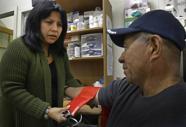 Laura Lopez, left, checks the blood pressure of Santos Aguilar Wednesday, Jan. 23, 2013, at the Street Level Health Project in Oakland, Calif. In trying to brand California�s new health care exchange, state officials had a hard time coming up with a name that signified health insurance, let alone one that would translate well into other languages such as Spanish, Chinese, Tagalog and Vietnamese. The exchange�s 5-member board settled on �Covered California� and is currently testing tag lines to see which words resonate best in focus groups. Lopez applauds the exchange for pledging to offer written materials in different languages. But she says the state will have to commit to providing one-on-one interpretive resources because some are illiterate, some don�t believe they are qualified for assistance, and some don�t know how to advocate for themselves. Many families will also have members with different legal statuses. Covered California estimates there are 5.6 million Californians without health insurance, or 16 percent of the population under age 65. Of that number, 4.6 million people are eligible for coverage under the Affordable Care Act and one million are ineligible due to their immigration status. �It�s another big population that�s left behind,� Lopez said. (AP Photo/Ben Margot)