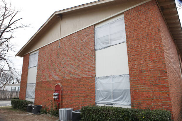 Plastic sheets are used to cover hail-damaged windows Monday at the West Oak Apartments, 24th Avenue SW and Brooks Street in Norman. PHOTOS BY DAVID MCDANIEL, THE OKLAHOMAN