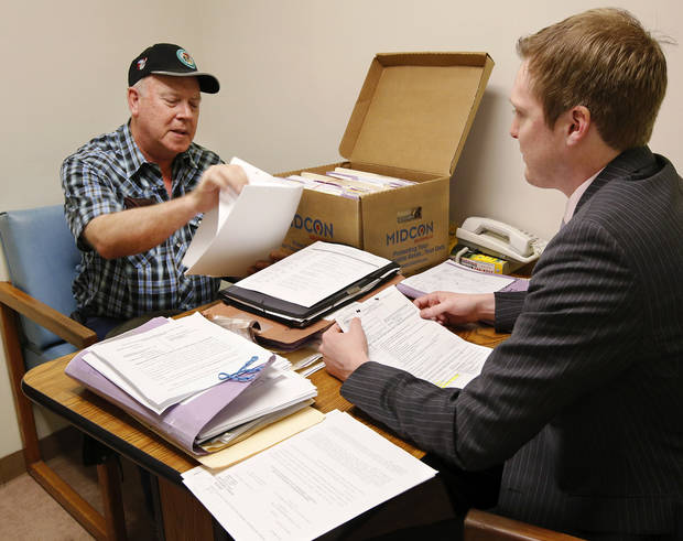 Fred Krueger, claimant,  meets with his attorney, Alex Forbes, right, to review forms and statements prior to being called to appealer in front of a judge at  Workers Compensation Court in the Denver Davison Building near the state Capitol on Thursday,  Feb. 21, 2013.   Photo by Jim Beckel, The Oklahoman