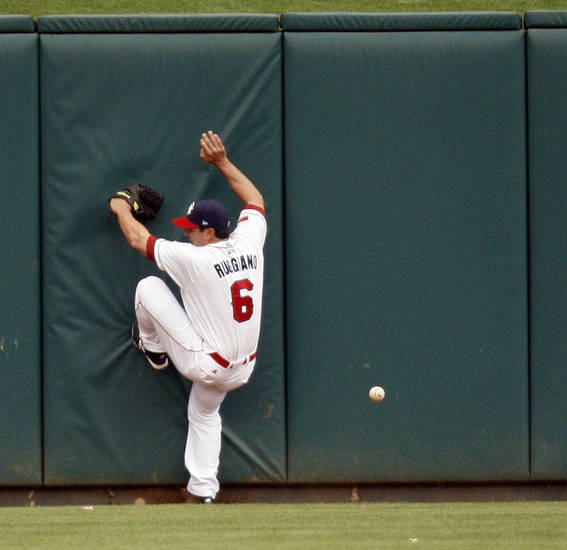 Oklahoma City's Justin Ruggiano (6) hits the wall while trying to catch a ball hit by Nashville's Caleb Gindl (15) in the first inning during the baseball game between the Oklahoma City RedHawks and the Nashville Sounds at the Chickasaw Bricktown Ballpark, in Oklahoma City, Monday, April 9, 2012. Gindl tripled on the play. Photo by Nate Billings, The Oklahoman